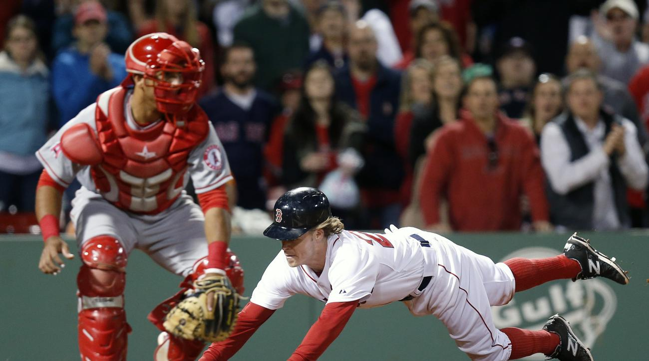 Boston Red Sox's Brock Holt, right, scores on a single by Blake Swihart as Los Angeles Angels' Carlos Perez waits for the throw during the eighth inning of a baseball game in Boston, Saturday, May 23, 2015. (AP Photo/Michael Dwyer)