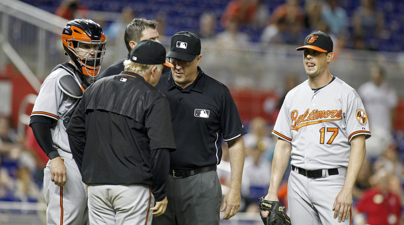 Baltimore Orioles relief pitcher Brian Matusz (17) waits as umpire Paul Emmel, center, speaks with Orioles manager Buck Showalter, as catcher Caleb Joseph stands nearby during the 12th inning of a baseball game in Miami, Saturday, May 23, 2015. Matusz lef