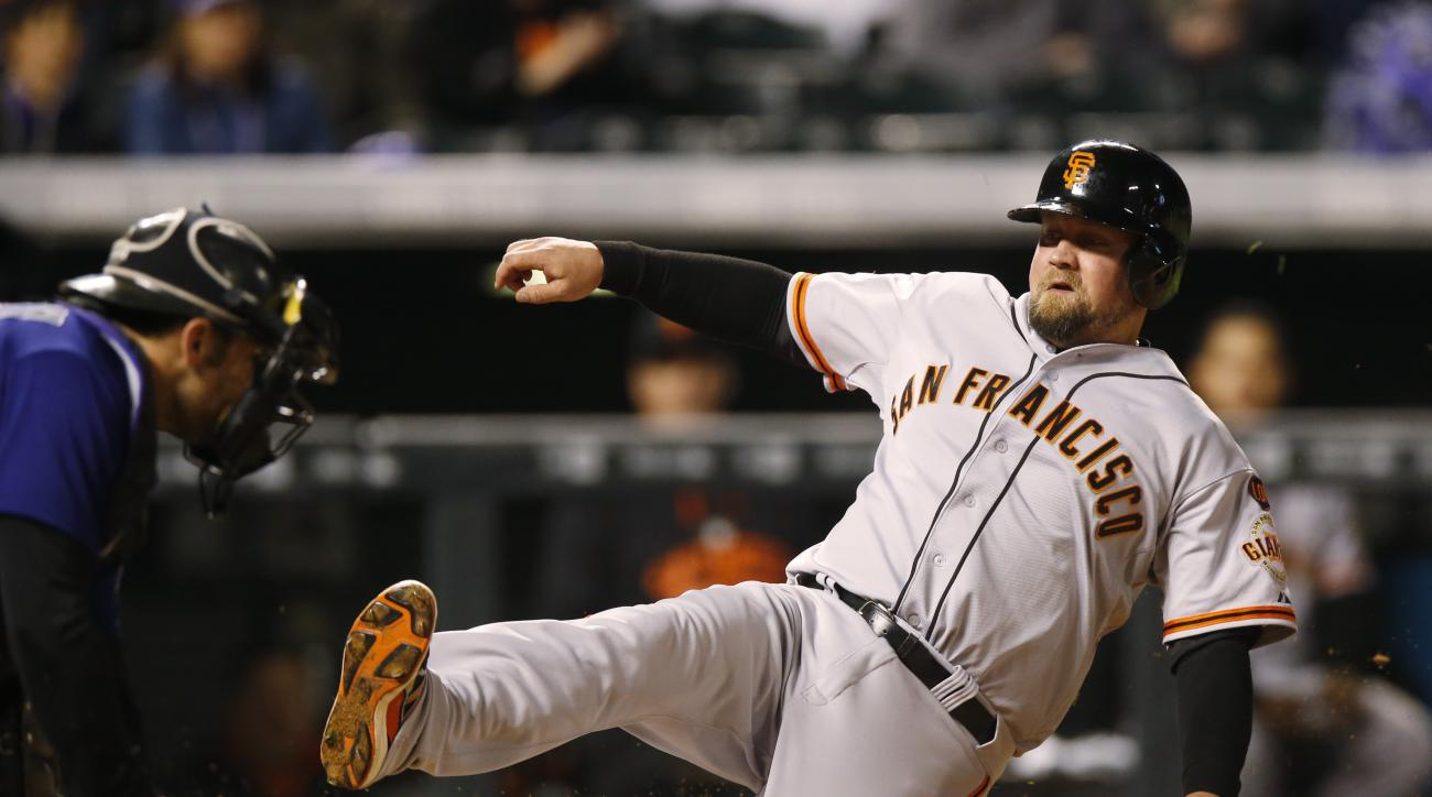 Colorado Rockies catcher Michael McKenry, left, applies the tag to put out San Francisco Giants' Casey McGehee at home plate during the fifth inning of the second game of a baseball doubleheader Saturday, May 23, 2015, in Denver. (AP Photo/David Zalubowsk
