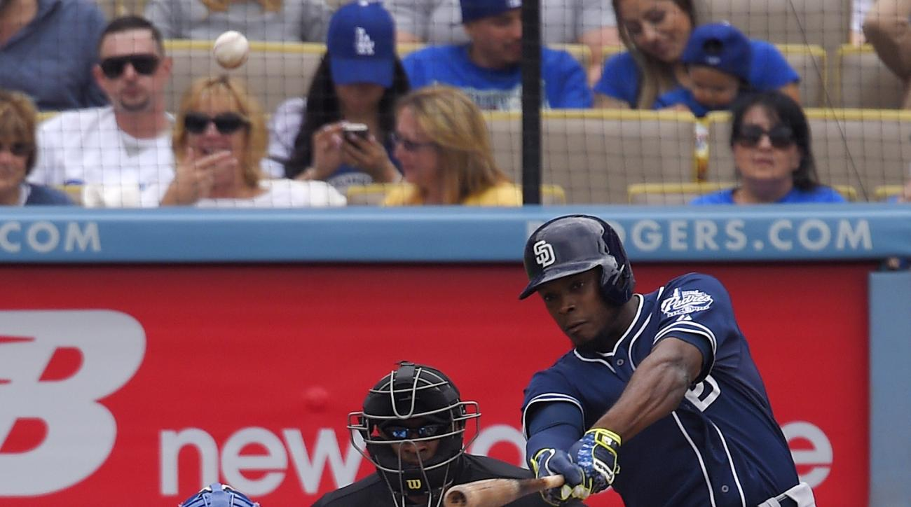 San Diego Padres' Justin Upton, right, hits a grand slam while Los Angeles Dodgers catcher Austin Barnes, left, and home plate umpire Alan Porter watch during the first inning of a baseball game, Sunday, May 24, 2015, in Los Angeles. (AP Photo/Mark J. Ter