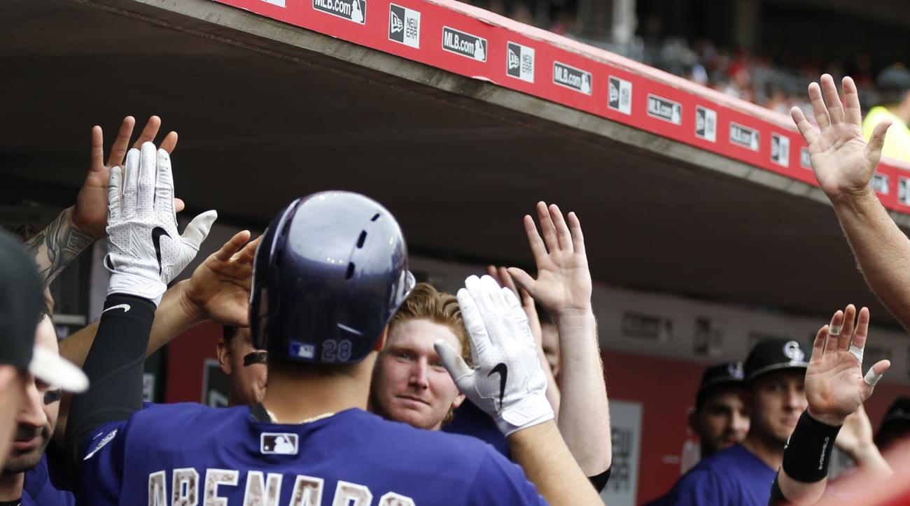Colorado Rockies' third baseman Nolan Arenado (28) is congratulated by teammates following a solo home run off Cincinnati Reds' starting pitcher Jason Marquis (31) during the fourth inning of their baseball game Monday, May 25, 2015,  in Cincinnati. (AP P