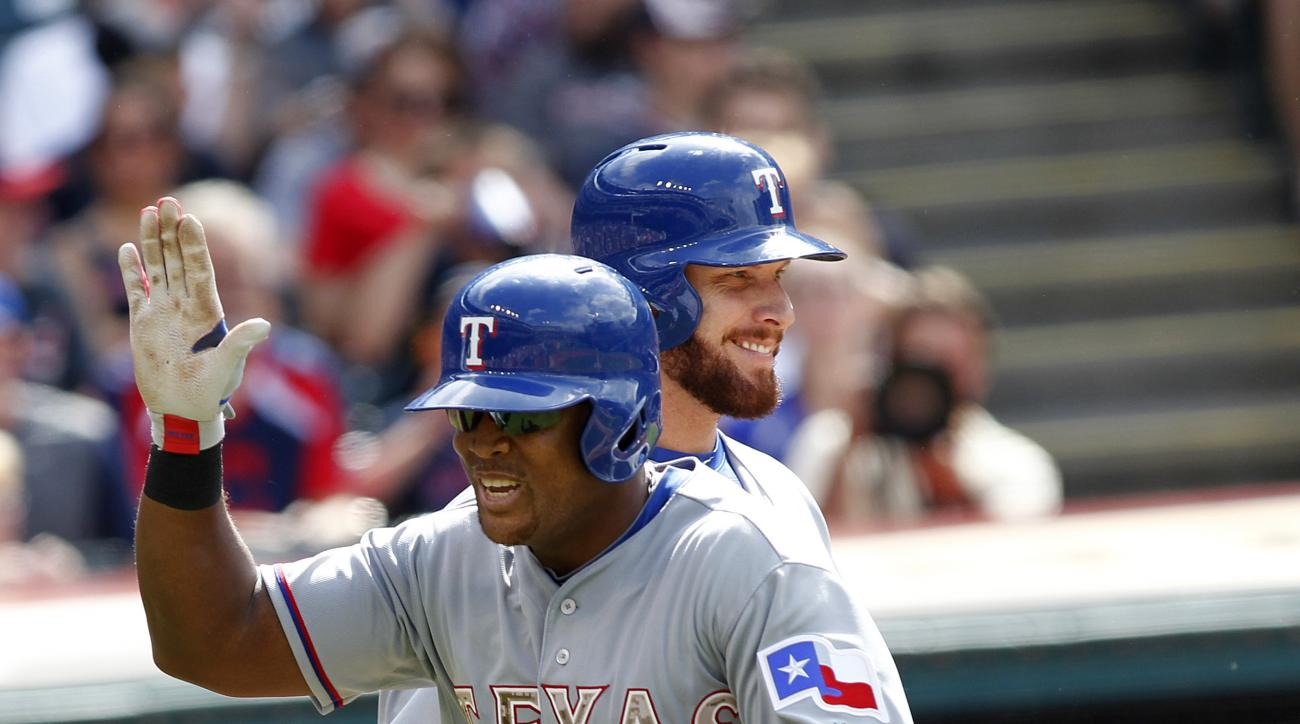 Texas Rangers Adrian Beltre is congratulated by Josh Hamilton after hitting a solo-home run during the first inning of a baseball game against the Cleveland Indians, Monday, May 25, 2015, in Cleveland. (AP Photo/Aaron Josefczyk)