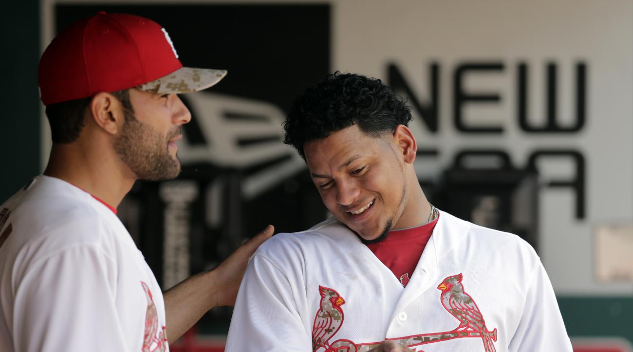St. Louis Cardinals starting pitcher Carlos Martinez, right, talks with teammate Jaime Garcia in the dugout after working the sixth inning of a baseball game against the Arizona Diamondbacks, Monday, May 25, 2015, in St. Louis. (AP Photo/Jeff Roberson)