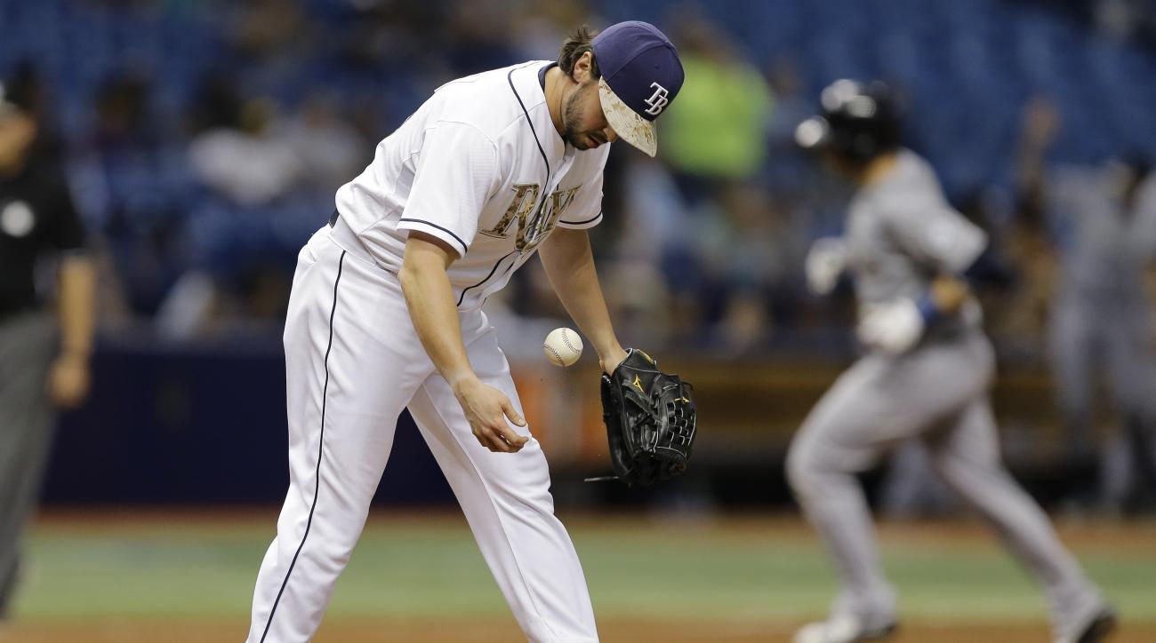Tampa Bay Rays relief pitcher Brandon Gomes drops a new baseball as Seattle Mariners' Mike Zunino runs around the bases after hitting a home run during the ninth inning of a baseball game Monday, May 25, 2015, in St. Petersburg, Fla.  The Mariners won the