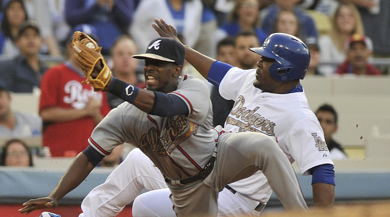 Atlanta Braves third baseman Pedro Ciriaco, left, holds up the ball after getting Los Angeles Dodger Juan Uribe out on a fielder's choice during the seventh inning of a baseball game in Los Angeles, Monday, May 25, 2015. (AP Photo/Richard Hartog)