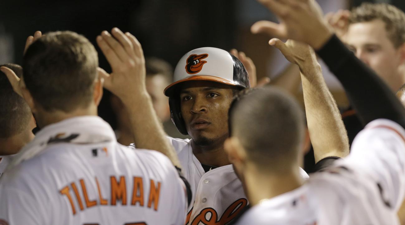 Baltimore Orioles' Jimmy Paredes, center, high-fives teammates in the dugout after scoring on a sacrifice fly ball by Chris Davis in the sixth inning of a baseball game against the Houston Astros, Tuesday, May 26, 2015, in Baltimore. (AP Photo/Patrick Sem