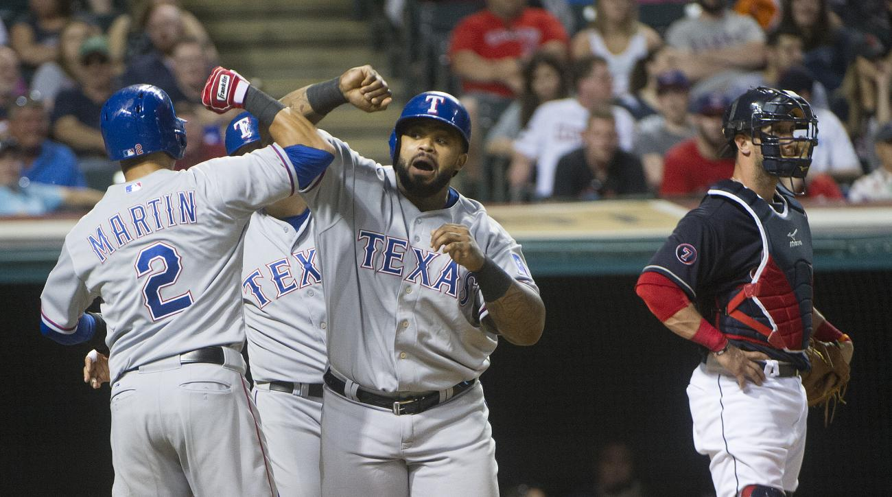 Texas Rangers' Prince Fielder is greeted at home plate by Lenoys Martin (2) and Shin-Soo Choo, after hitting a  three-run home run off Cleveland Indians' Danny Salazar during the fifth inning of a baseball game in Cleveland, Tuesday, May 26, 2015. Indians