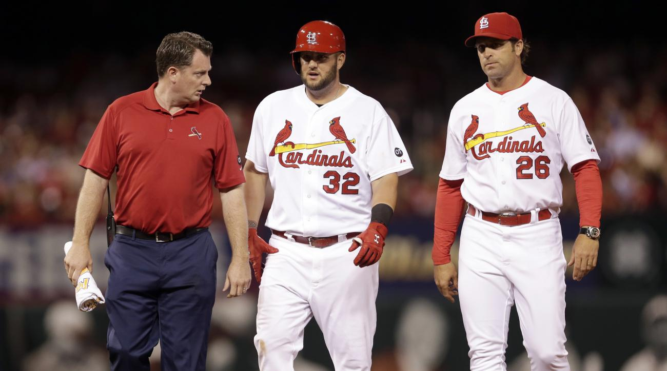 St. Louis Cardinals' Matt Adams, center, walks off the field after being checked on by Cardinals trainer Chris Conroy, left, and manager Mike Matheny after an injury during the fifth inning of a baseball game against the Arizona Diamondbacks Tuesday, May