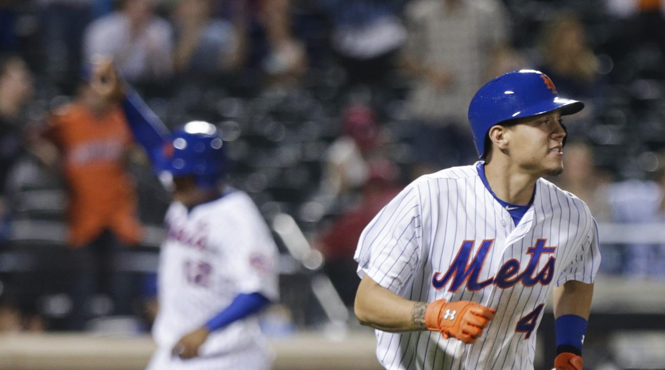 New York Mets' Wilmer Flores (4) runs to first base after hitting  an RBI single to during the tenth inning to win  a baseball game against the Philadelphia Phillies Tuesday, May 26, 2015, in New York. The Mets won 5-4. (AP Photo/Frank Franklin II)