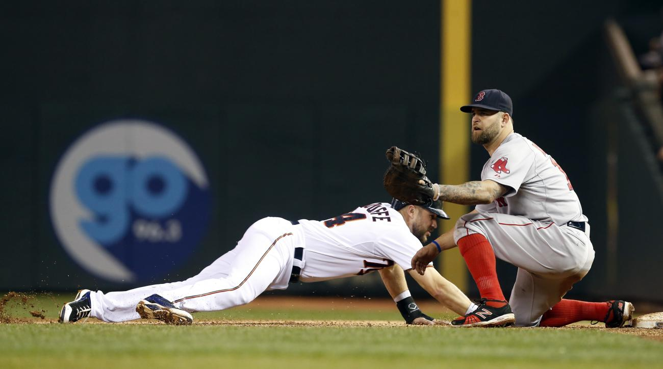 Minnesota Twins' Trevor Plouffe, left, dives safely back to first on a pick-off attempt by Boston Red Sox first baseman Mike Napoli during the fourth inning of a baseball game, Tuesday, May 26, 2015, in Minneapolis. (AP Photo/Jim Mone)