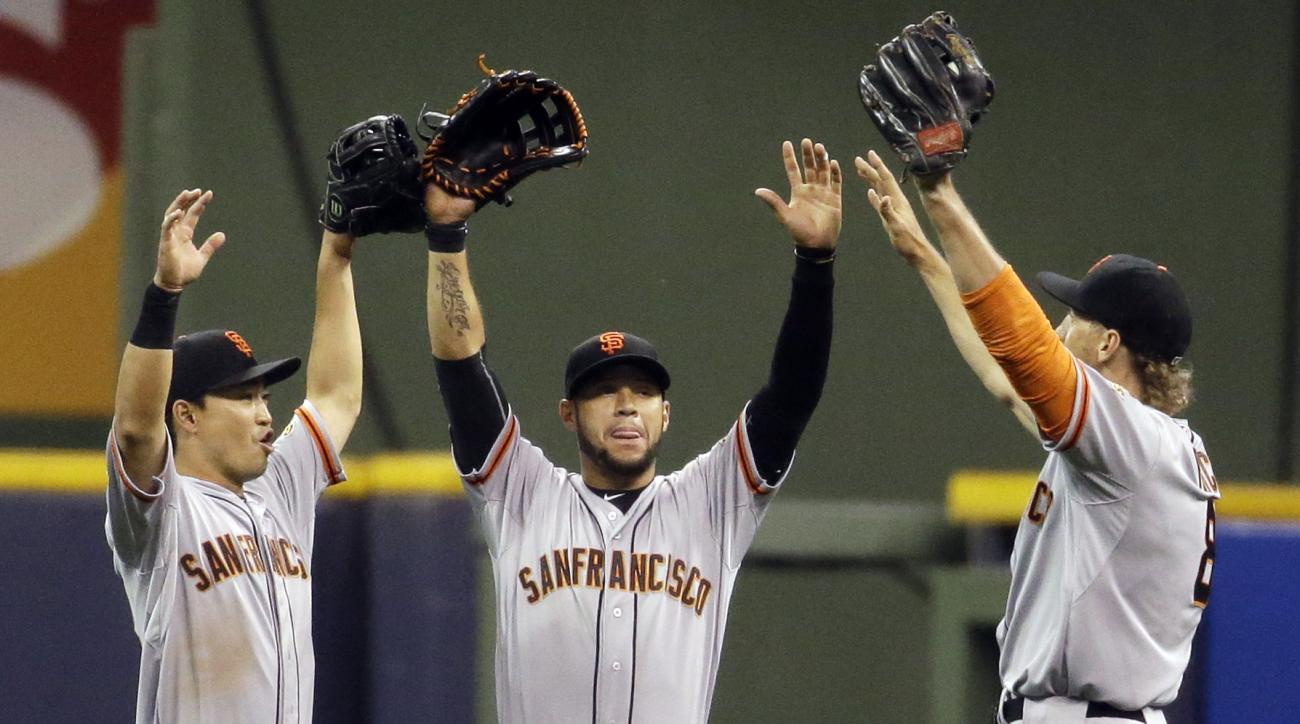 San Francisco Giants' Nori Aoki, left to right, Gregor Blanco and Hunter Pence celebrate after a baseball game against the Milwaukee Brewers Tuesday, May 26, 2015, in Milwaukee. The Giants won 6-3. (AP Photo/Morry Gash)