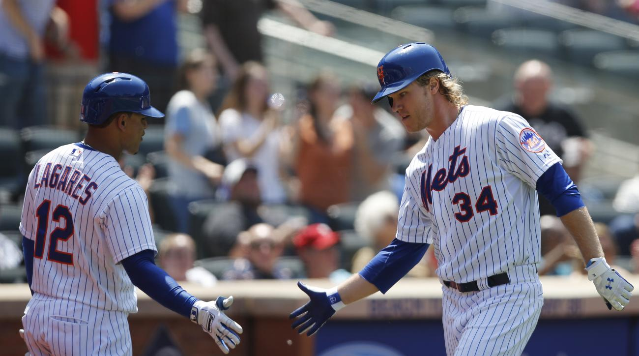 New York Mets' Juan Lagares (12) greets  New York Mets starting pitcher Noah Syndergaard after Syndergaard hit a fourth-inning, solo home run in a baseball game against the Philadelphia Phillies in New York, Wednesday, May 27, 2015. (AP Photo/Kathy Willen