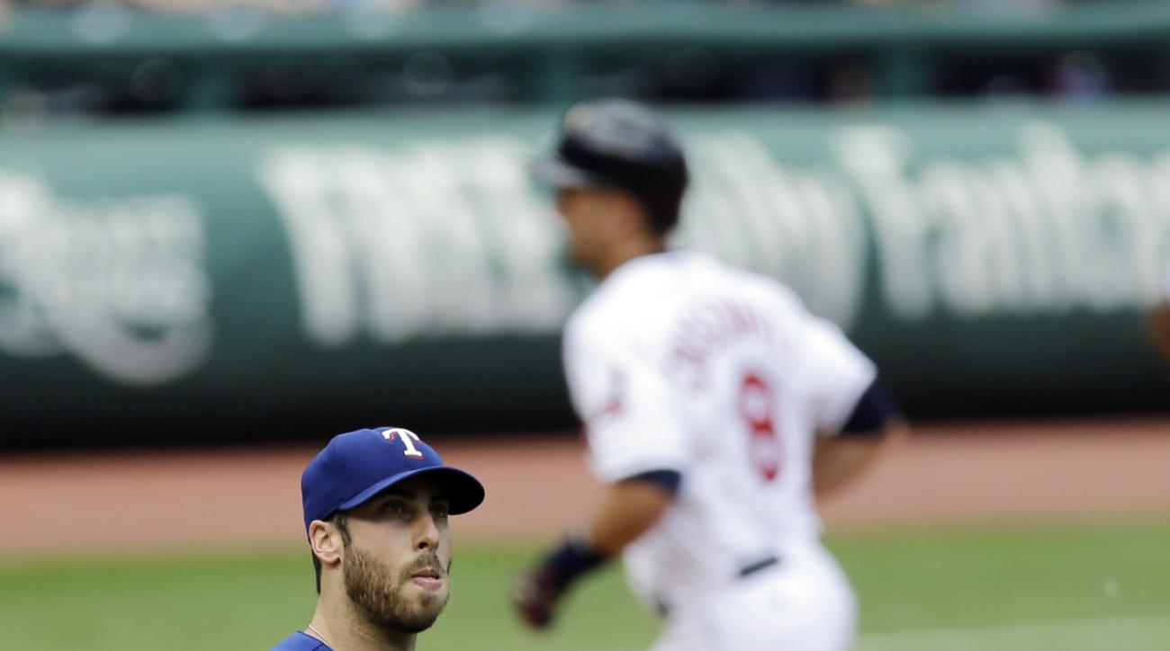 Texas Rangers relief pitcher Anthony Bass, left, waits for Cleveland Indians' Lonnie Chisenhall to run the bases after hitting a solo home run in the fourth inning of a baseball game, Wednesday, May 27, 2015, in Cleveland. The Indians defeated the Rangers