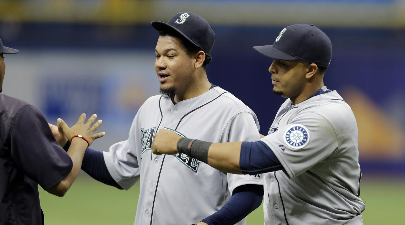 Seattle Mariners' Nelson Cruz, right, and starting pitcher Felix Hernandez, center, celebrate with teammates after the team's 3-0 win over the Tampa Bay Rays during a baseball game Wednesday, May 27, 2015, in St. Petersburg, Fla.  Hernandez pitched a comp