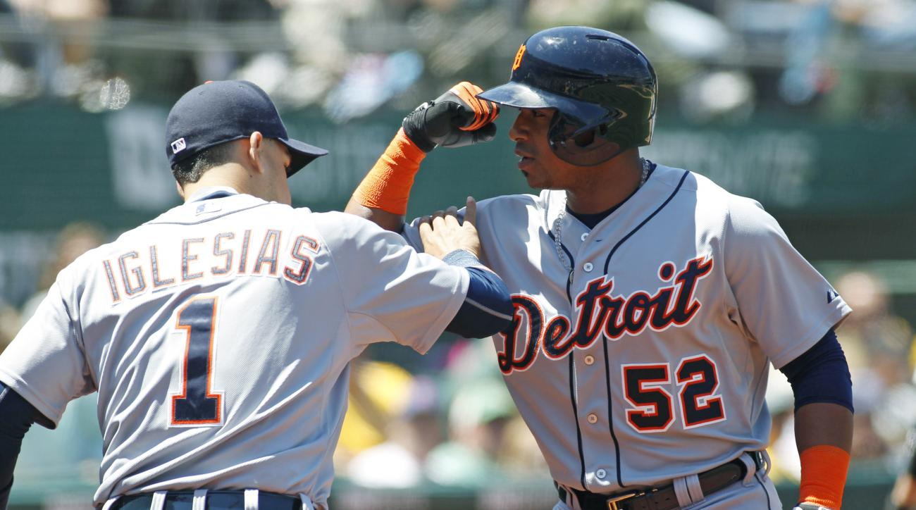 Detroit Tigers Yoenis Cespedes (52) celebrates with teammate Jose Iglesias after hitting a three run homer against the Oakland Athletics during the fifth inning of a baseball game, Wednesday, May 27, 2015, in Oakland, Calif. (AP Photo/George Nikitin)