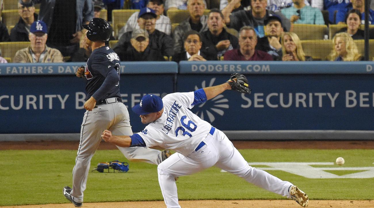 Atlanta Braves' Andrelton Simmons, left, scores on a wild pitch as Los Angeles Dodgers relief pitcher Adam Liberatore misses the throw to the plate during the eighth inning of a baseball game, Wednesday, May 27, 2015, in Los Angeles. (AP Photo/Mark J. Ter