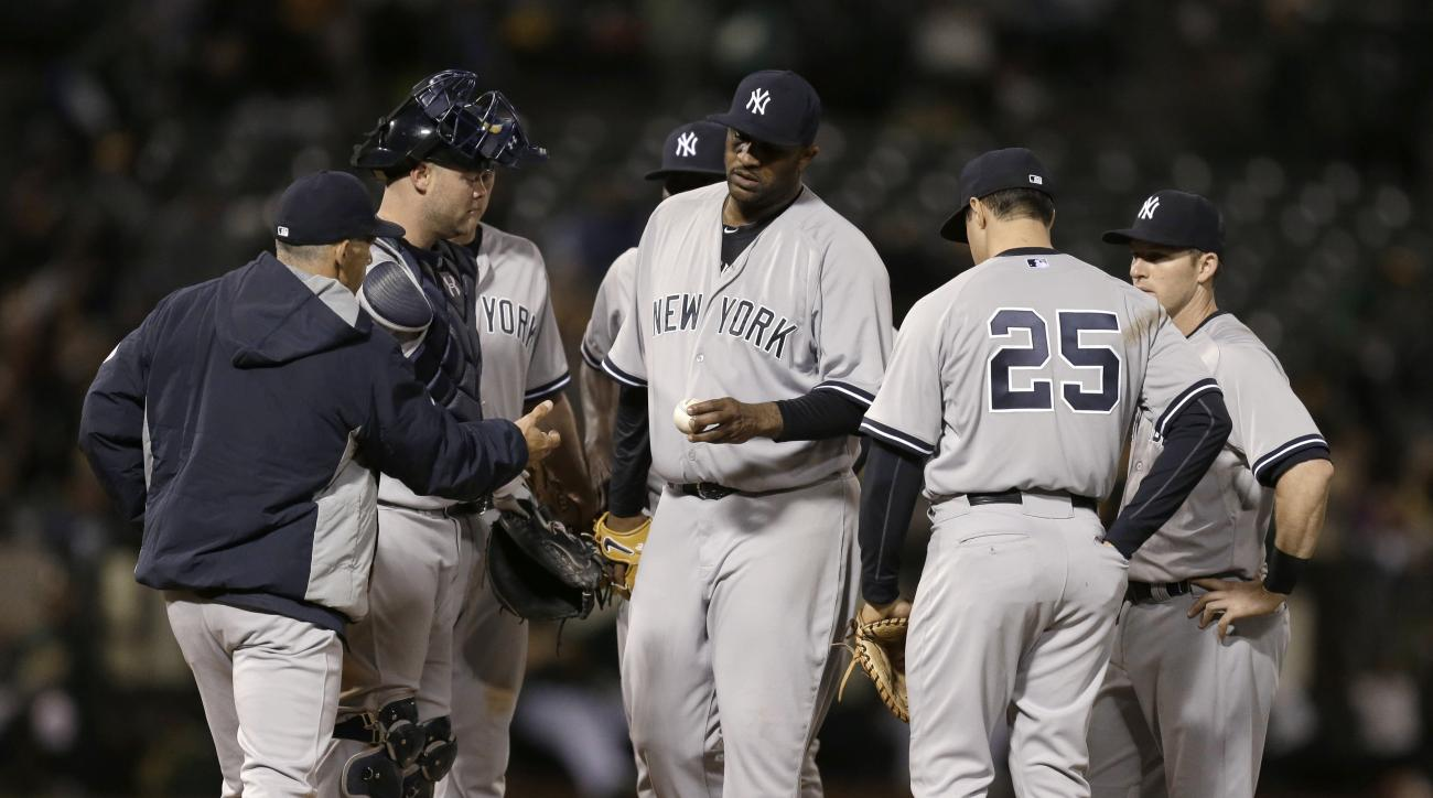 New York Yankees' CC Sabathia, center, hands the ball to manager Joe Girardi in the seventh inning of a baseball game against the Oakland Athletics on Thursday, May 28, 2015, in Oakland, Calif. (AP Photo/Ben Margot)