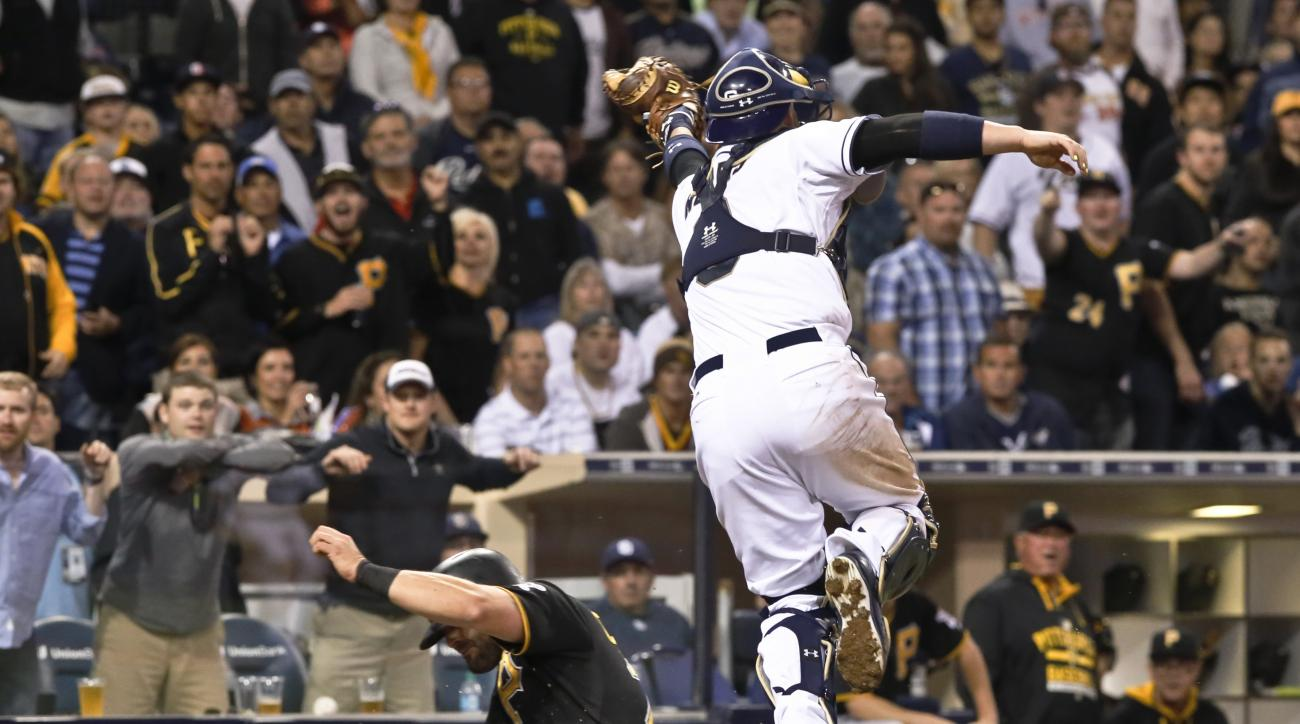 Pittsburgh Pirates' Francisco Cervelli scores on the high throw to San Diego Padres catcher Derek Norris during the sixth inning of a baseball game Thursday, May 28, 2015, in San Diego. (AP Photo/Don Boomer)