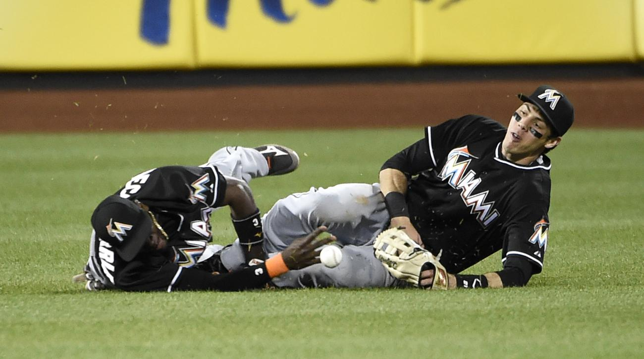 Miami Marlins shortstop Adeiny Hechavarria, left, and Miami Marlins left fielder Christian Yelich collide trying to catch New York Mets' Daniel Murphy's RBI double in the ninth inning of a baseball game at Citi Field on Friday, May 29, 2015, in New York.