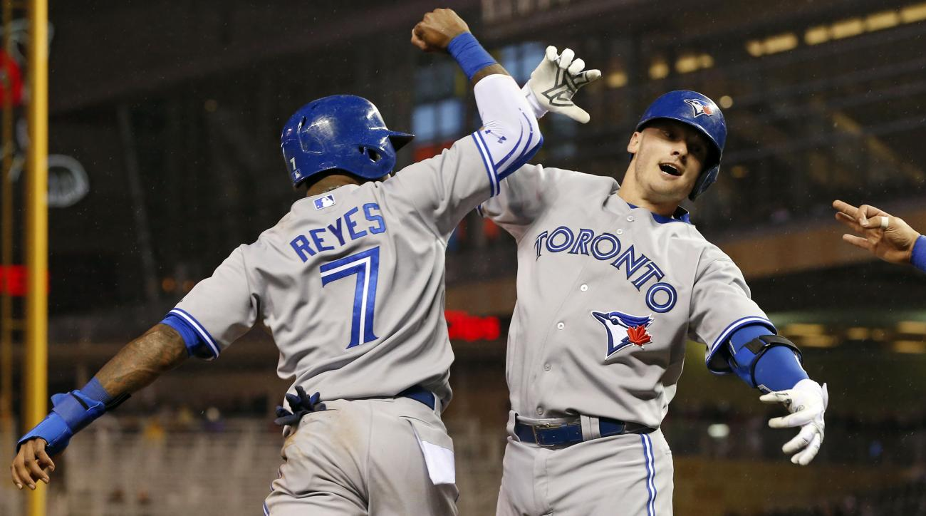 Toronto Blue Jays' Josh Donaldson, right, and Jose Reyes celebrate Donaldson's three-run home run off Minnesota Twins pitcher Trevor May in the fifth inning of a baseball game Friday, May 29, 2015, in Minneapolis. (AP Photo/Jim Mone)