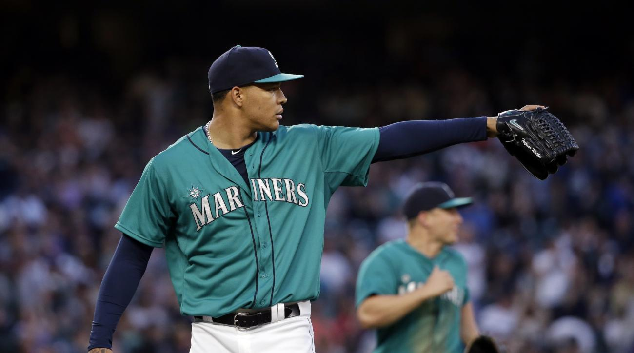Seattle Mariners starting pitcher Taijuan Walker points to a teammate after a play on a grounder by the Cleveland Indians in the sixth inning of a baseball game Friday, May 29, 2015, in Seattle. (AP Photo/Elaine Thompson)