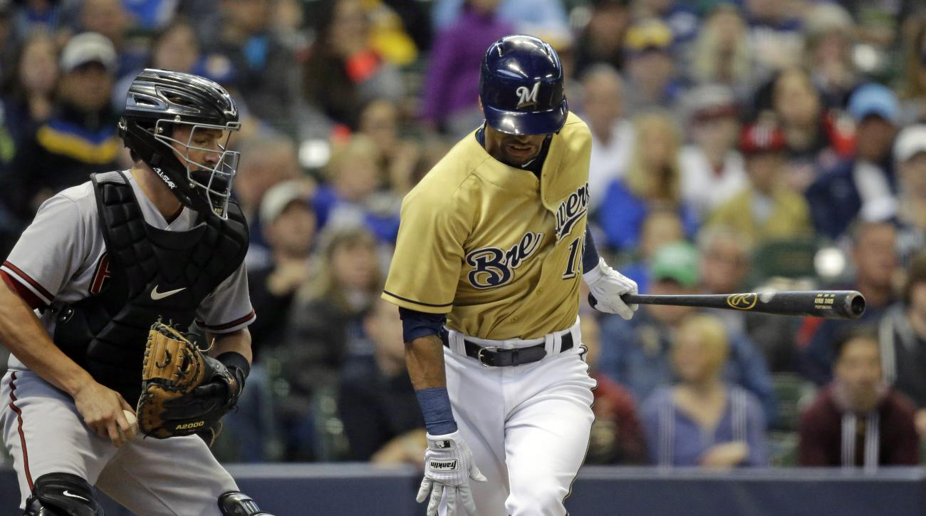 Milwaukee Brewers' Khris Davis, right, strikes out against the  Arizona Diamondbacks during the first inning of a baseball game Saturday, May 30, 2015, in Milwaukee. Davis departed after taking an awkward swing while striking out and said after the game t