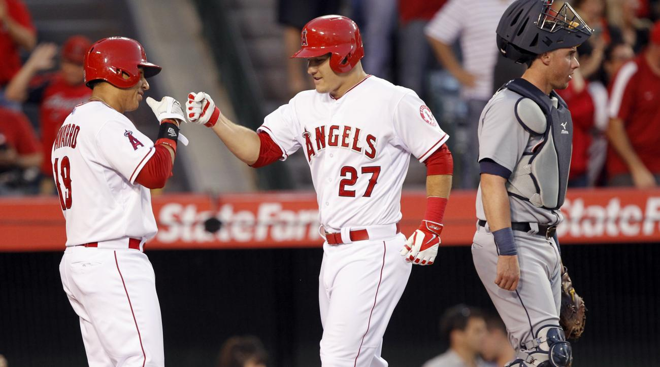 Los Angeles Angels' Efren Navarro, left, congratulates Mike Trout for scoring on a three-run home run by designated hitter Albert Pujols during the second inning, with Detroit Tigers catcher James McCann, right, looking on, in a baseball game in Anaheim,