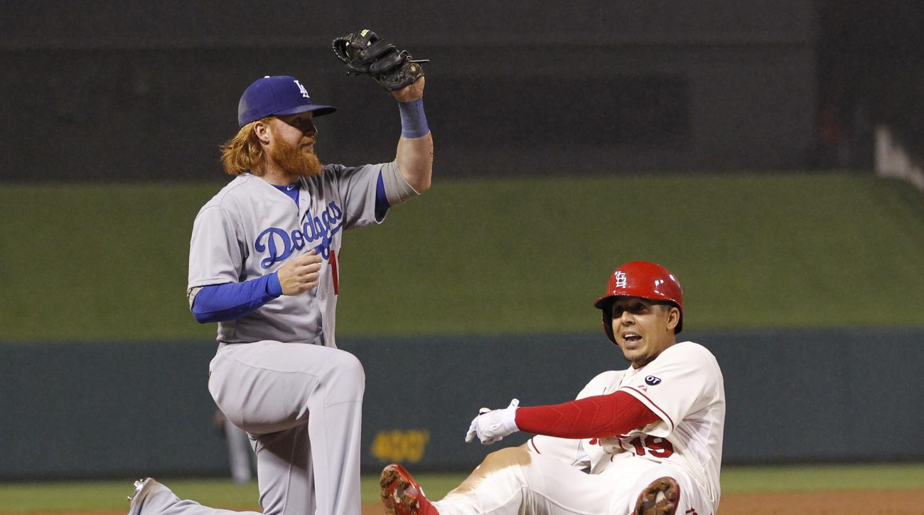 Los Angeles Dodgers third baseman Justin Turner, left, holds up his glove after tagging out St. Louis Cardinals' Jon Jay during the second inning of a baseball game Saturday, May 30, 2015, in St. Louis. (AP Photo/Billy Hurst)