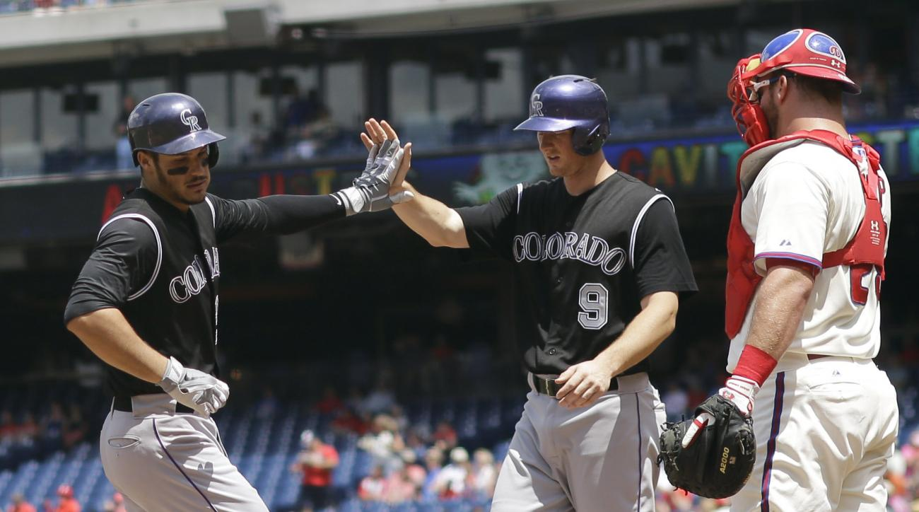 Colorado Rockies' Nolan Arenado, left, and DJ LeMahieu, center, celebrate past Philadelphia Phillies catcher Cameron Rupp after Arenado's two-run home run during the first inning of a baseball game, Sunday, May 31, 2015, in Philadelphia. (AP Photo/Matt Sl