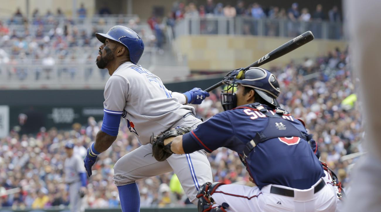 Toronto Blue Jays' Jose Reyes, left, watches the flight of his two-run single off Minnesota Twins relief pitcher J.R. Graham during the second inning of a baseball game in Minneapolis, Sunday, May 31, 2015. Twins catcher Kurt Suzuki, right, looks on. (AP