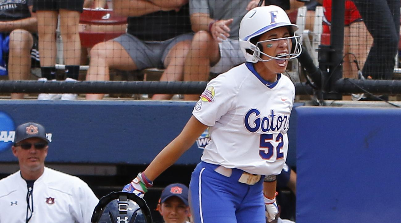 Florida's Justine McLean, back, celebrates after scoring in the ninth inning during an NCAA Women's College World Series softball game against Auburn in Oklahoma City, Sunday, May 31, 2015. Florida won 3-2. (AP Photo/Alonzo Adams)