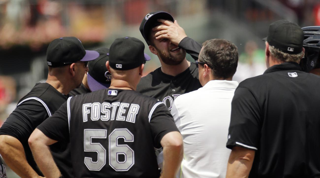 Colorado Rockies starting pitcher Jordan Lyles wipes his face as he talks with team personnel after suffering an injury during the second inning of a baseball game against the Philadelphia Phillies, Sunday, May 31, 2015, in Philadelphia. Lyles was pulled