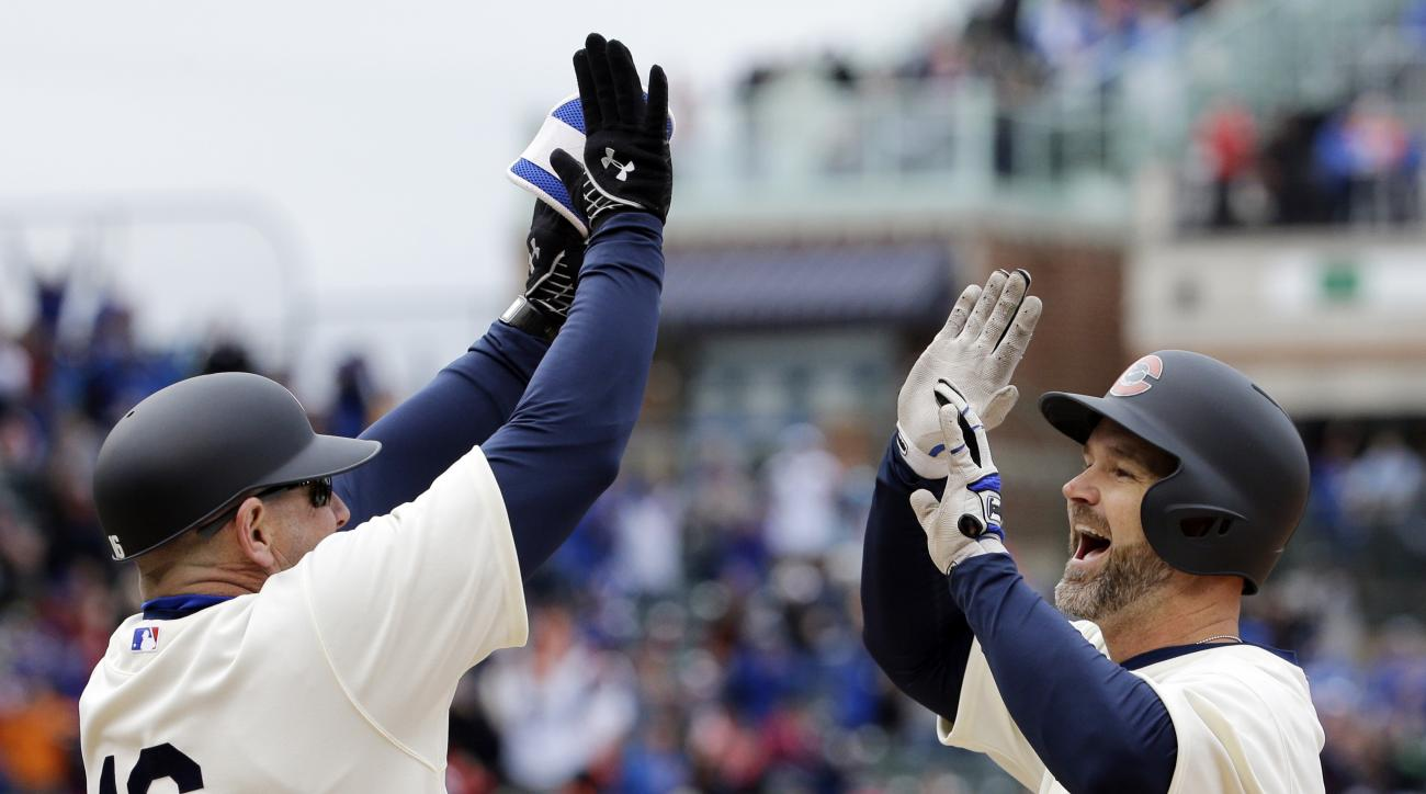Chicago Cubs' David Ross, right, celebrates with first base coach Brandon Hyde after hitting the game-winning single against the Kansas City Royals during the 11th inning of a baseball game, Sunday, May 31, 2015, in Chicago. The Cubs won 2-1. (AP Photo/Na