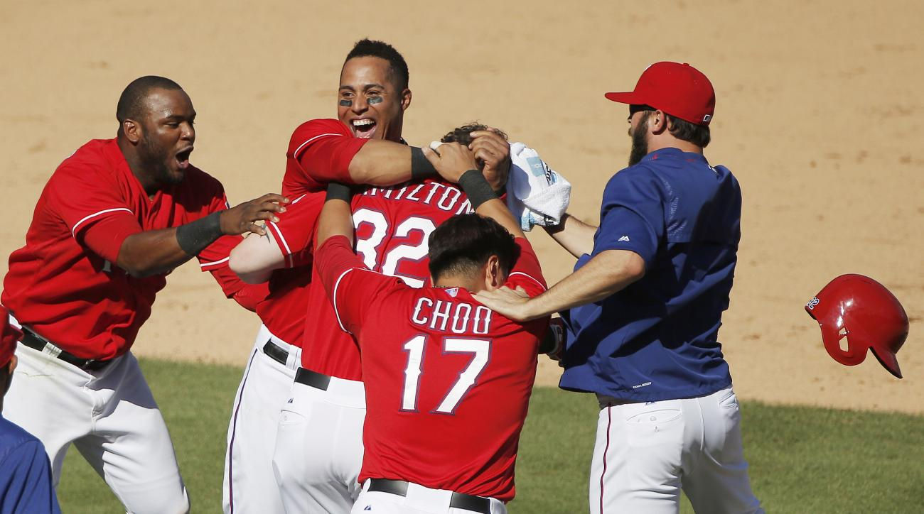 Texas Rangers' Josh Hamilton (32) is mobbed by teammates in celebration of his two-RBI walkoff hit during the ninth inning of a baseball game against the Boston Red Sox, Sunday, May 31, 2015, in Arlington, Texas. Texas won 4-3. (AP Photo/Brandon Wade)