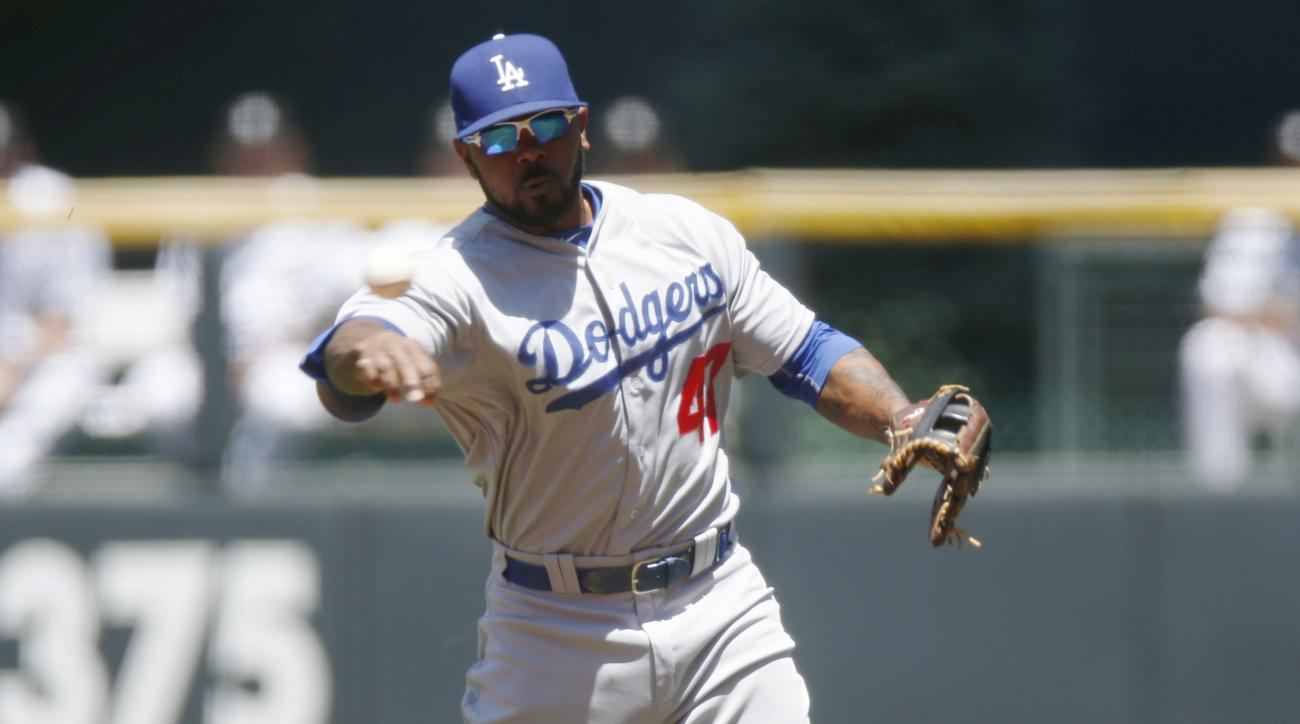 Los Angeles Dodgers second baseman Howie Kendrick throws out Colorado Rockies' Charlie Blackmon at first base during the first inning of game one in a baseball doubleheader, Tuesday, June 2, 2015, in Denver. (AP Photo/David Zalubowski)