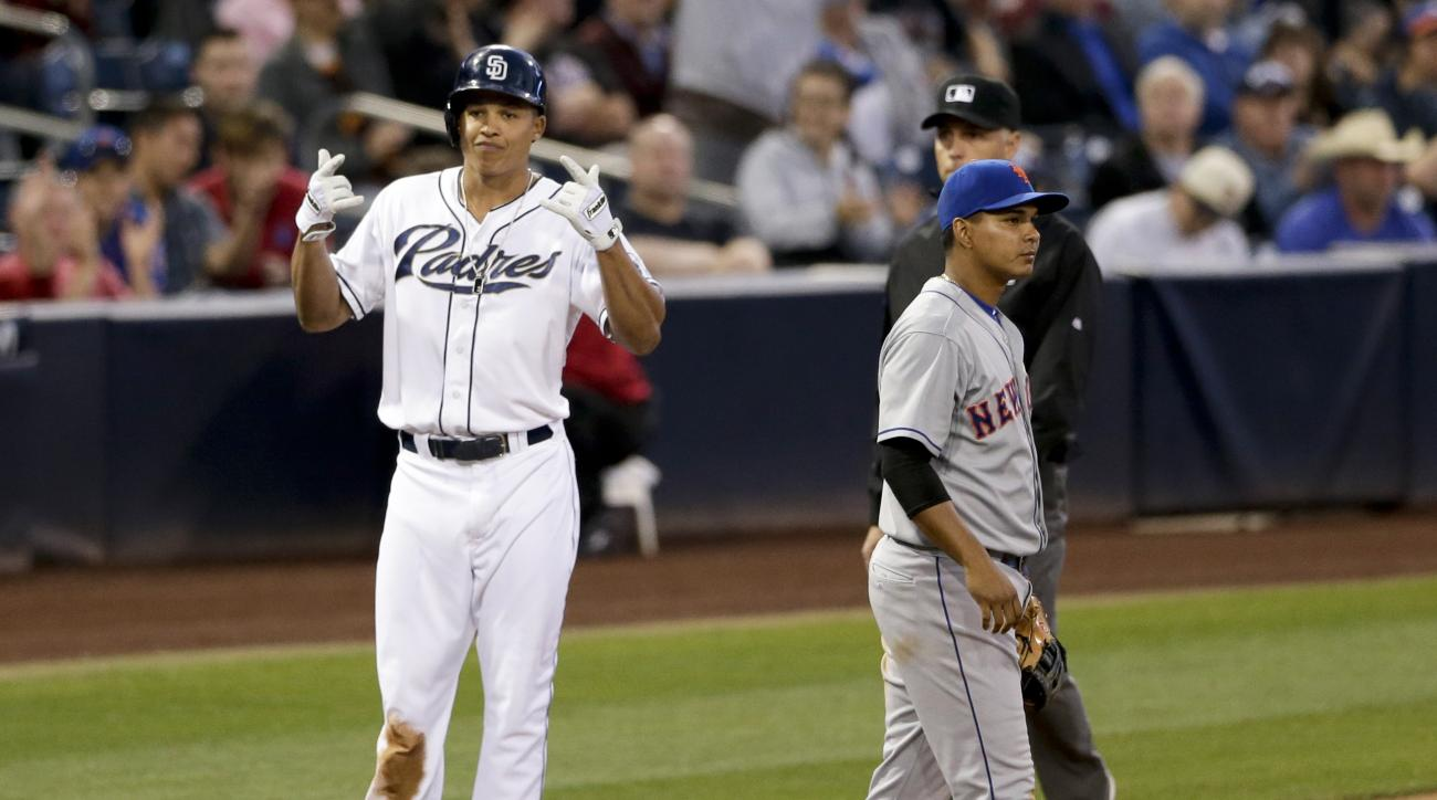San Diego Padres' Will Venable gestures toward teammates in the dugout after hitting a two-run triple, as New York Mets shortstop Ruben Tejada stands nearby during the second inning of a baseball game Tuesday, June 2, 2015, in San Diego. (AP Photo/Gregory
