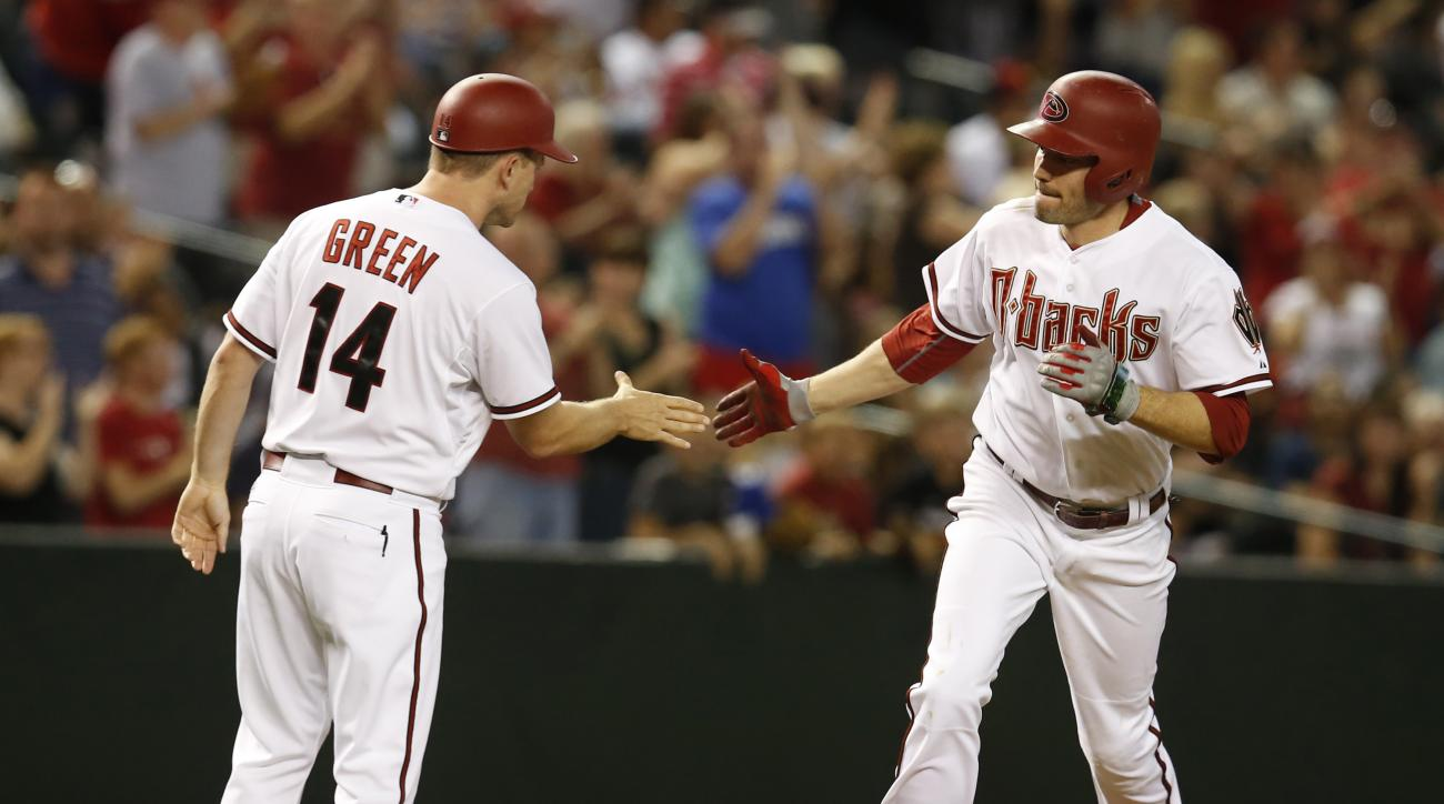 Arizona Diamondbacks A.J. Pollock, right, celebrates with third base coach Andy Green in the seventh inning after hitting a two-run home run against the Atlanta Braves during a baseball game, Tuesday, June 2, 2015, in Phoenix. (AP Photo/Rick Scuteri)