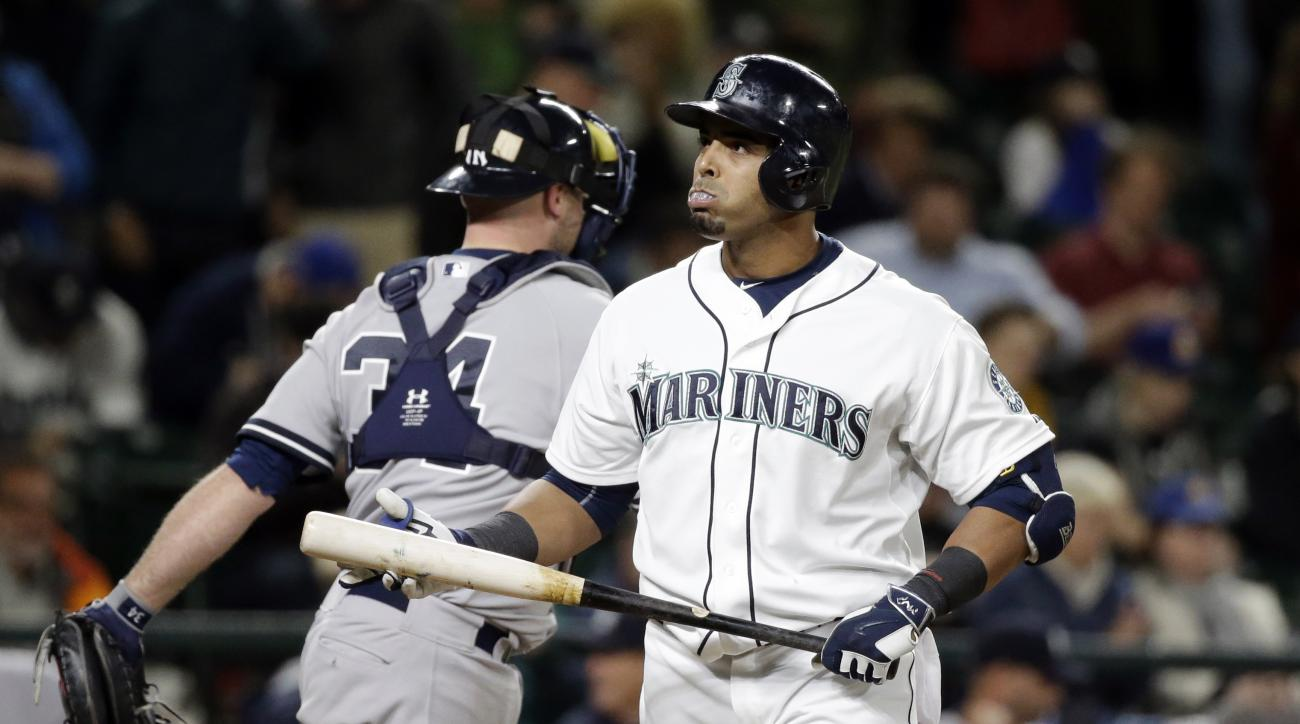 Seattle Mariners' Nelson Cruz, right, heads away from the plate after striking out to end the baseball game in the 11th inning as New York Yankees catcher Brian McCann leaves the field Tuesday, June 2, 2015, in Seattle. The Yankees won 5-3 in 11 innings.