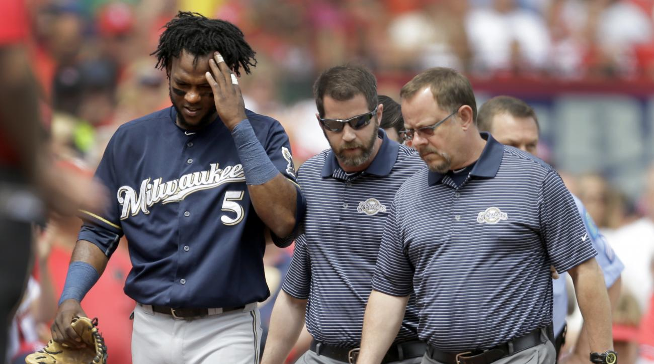 Milwaukee Brewers second baseman Hector Gomez (5) rubs his head as he is helped off the field by trainers after diving into the crowd after a foul ball by St. Louis Cardinals' Jason Heyward during the sixth inning of a baseball game, Wednesday, June 3, 20