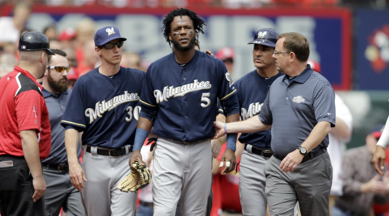 Milwaukee Brewers second baseman Hector Gomez (5) walks off the field after diving into the crowd after a foul ball by St. Louis Cardinals' Jason Heyward during the sixth inning of a baseball game Wednesday, June 3, 2015, in St. Louis. Gomez left the game