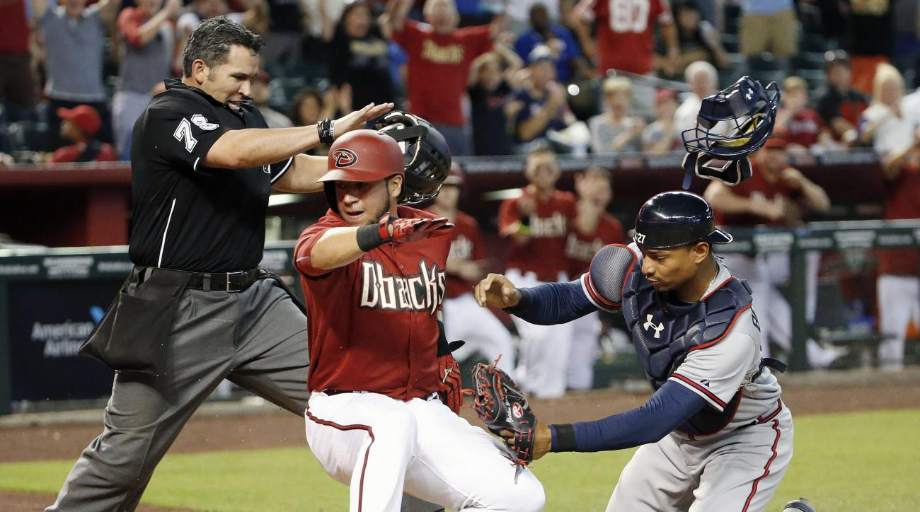Arizona Diamondbacks' David Peralta, middle, scores a run ahead to the tag by Atlanta Braves' Christian Bethancourt, right, as umpire Manny Gonzalez starts call the runner safe during the seventh inning of a baseball game Wednesday, June 3, 2015, in Phoen