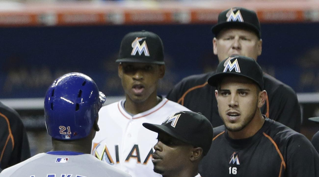 Miami Marlins' Dee Gordon, center, holds back Chicago Cubs' Junior Lake (21) as Lake and Marlins' Jose Fernandez, right, exchange words after Lake hit a home run scoring Anthony Rizzo during the sixth inning of a baseball game, Wednesday, June 3, 2015, in