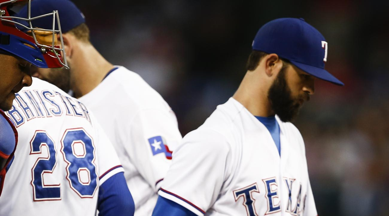 Texas Rangers starting pitcher Nick Martinez, right, leaves the game after being relieved of his duties by manager Jeff Banister (28) during the third inning of a baseball game against the Chicago White Sox, Wednesday, June 3, 2015, in Arlington, Texas. (
