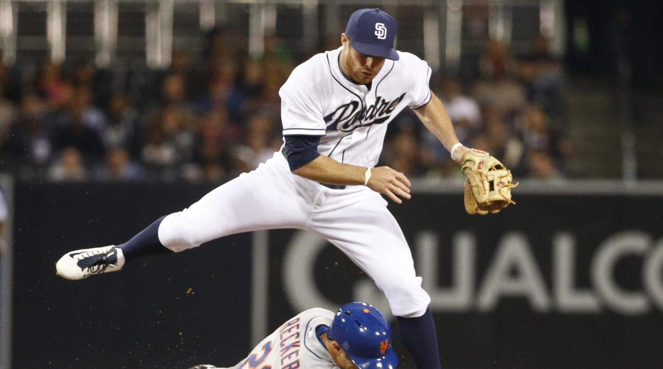 San Diego Padres second baseman Cory Spangenberg hurdles New York Mets' Anthony Recker while relaying to first to complete a inning-ending double play in the seventh inning of baseball game Wednesday, June 3, 2015, in San Diego. Eric Campbell was out at f