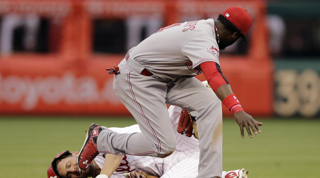 Cincinnati Reds second baseman Brandon Phillips, right, tags out Philadelphia Phillies' Jeff Francoeur at second as Francoeur tried to advance on a fly out by Chase Utley during the third inning of a baseball game, Thursday, June 4, 2015, in Philadelphia.