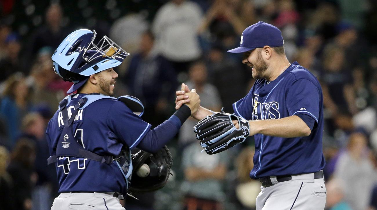 Tampa Bay Rays catcher Rene Rivera, left, and closing pitcher Kevin Jepsen share congratulations after the Rays defeated the Seattle Mariners 2-1 in a baseball game Thursday, June 4, 2015, in Seattle. (AP Photo/Elaine Thompson)