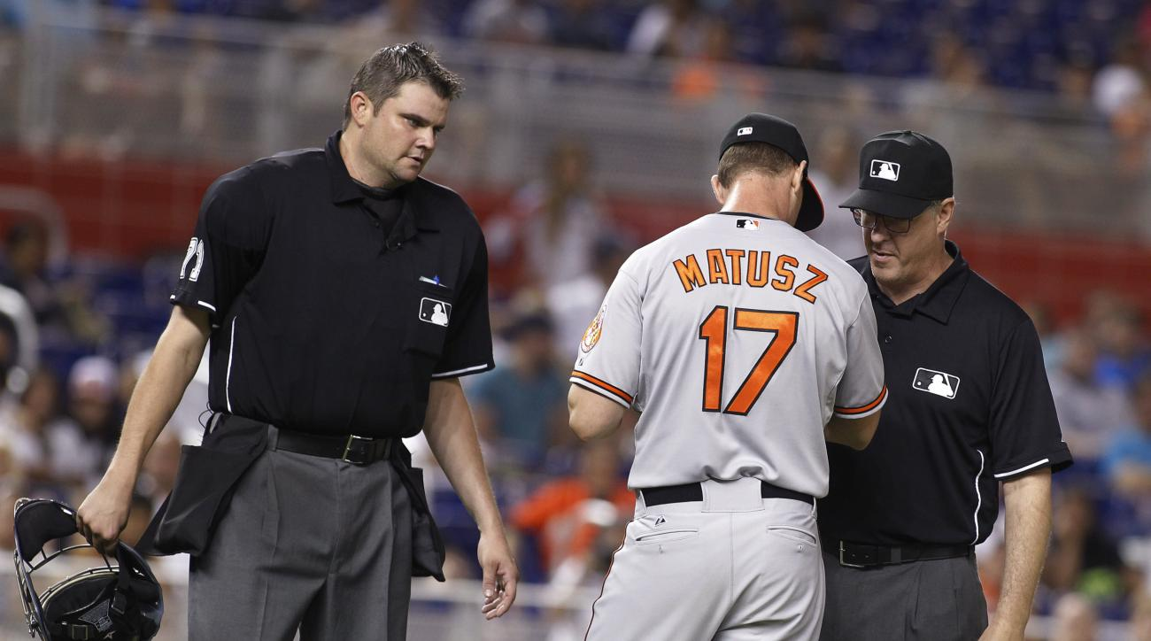 Baltimore Orioles relief pitcher Brian Matusz (17) speaks with umpires Paul Emmel, right,and Jordan Baker, left, in the 12th inning during a baseball game in Miami, Saturday, May 23, 2015. Matusz left the game after his forearm was inspected. (AP Photo/Jo
