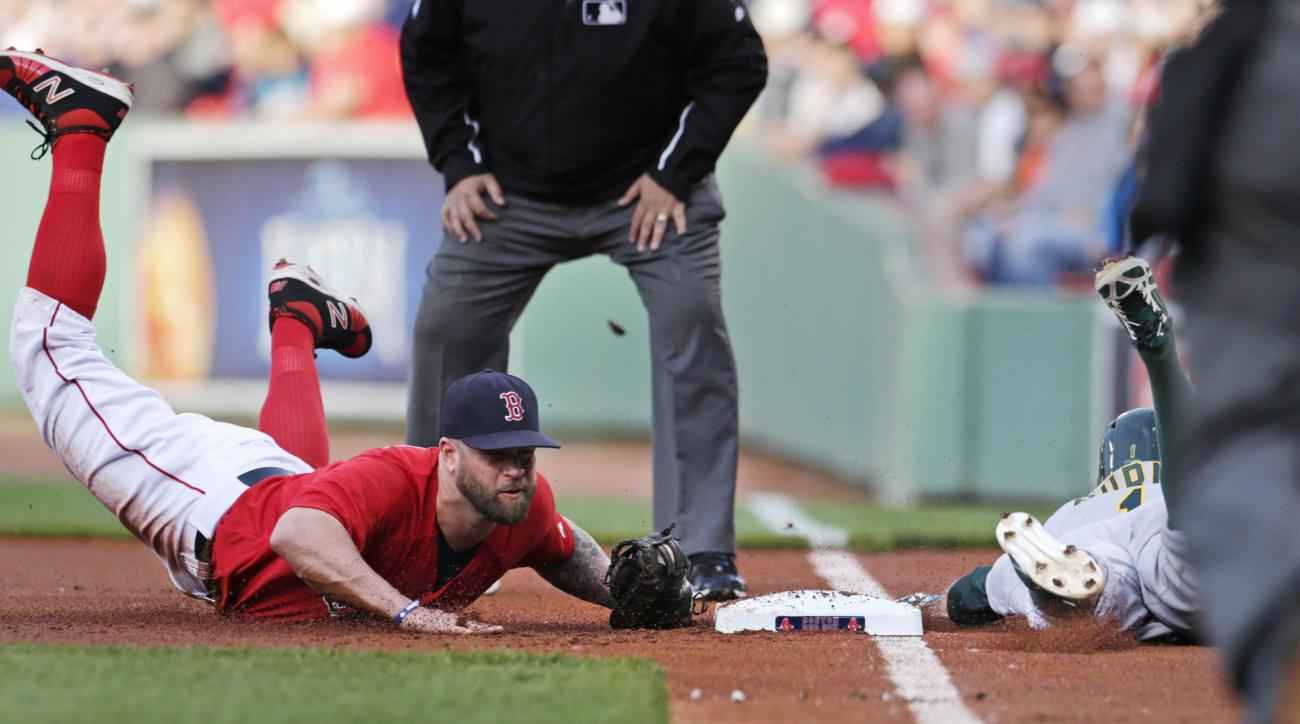 Boston Red Sox first baseman Mike Napoli, left, dives to tag the bag as Oakland Athletics' Billy Burns is caught on a ground out in the first inning during a baseball game at Fenway Park in Boston, Friday, June 5, 2015. (AP Photo/Charles Krupa)