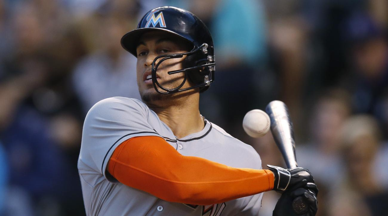 Miami Marlins' Giancarlo Stanton has the ball that he fouled bounce off his bat as he follows through with his swing on a pitch from Colorado Rockies startier Eddie Butler in the fifth inning of a baseball game Friday, June 5, 2015, in Denver. (AP Photo/D