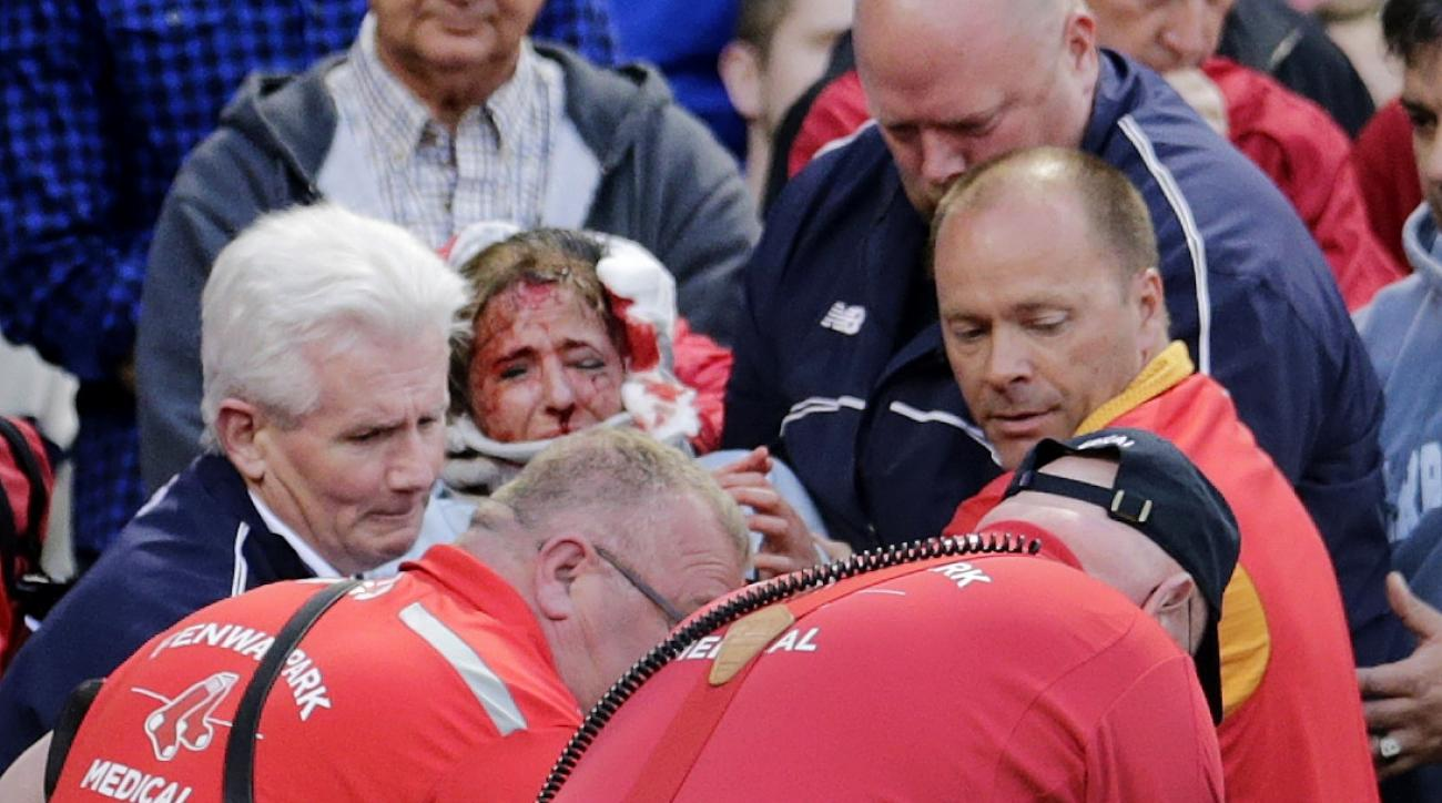 A fan, who was accidentally hit in the head with a broken bat by Oakland Athletics' Brett Lawrie, is helped from the stands during a baseball game against the Boston Red Sox at Fenway Park in Boston, Friday, June 5, 2015.  The game was stopped while they